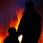 The silhouette of a man and his child in front of a fire.